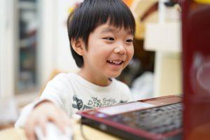 笑顔でパソコンにむかう少年