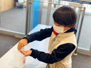 マスク姿で消毒する少年