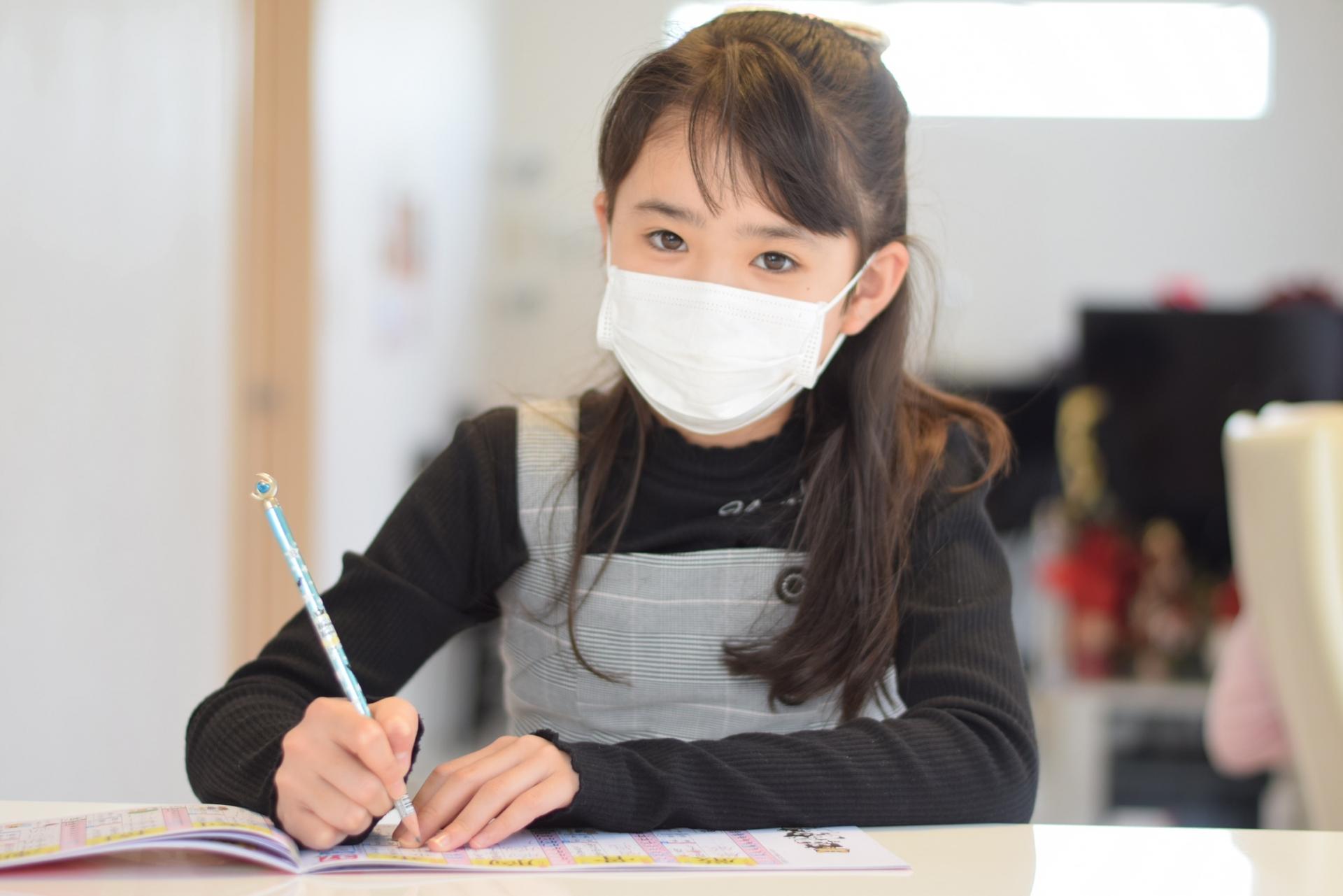 マスクで勉強する少女